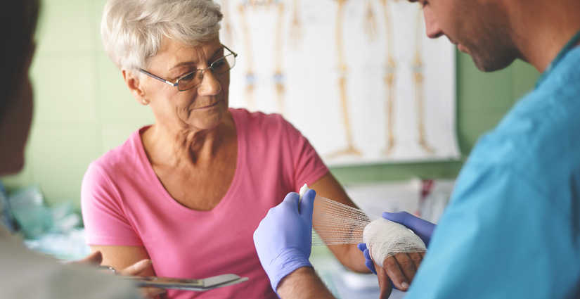 Woman receiving would care treatment to her left hand